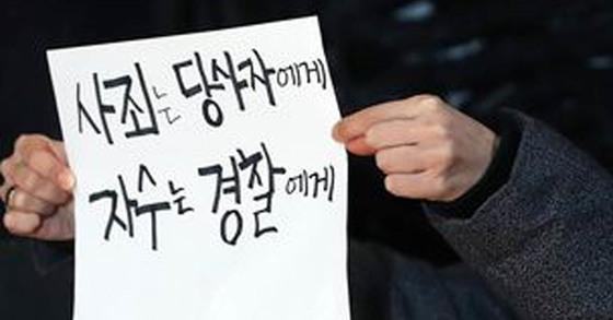 이윤택 연출가의 기자회견장에서 한 시민이 '사죄는 당사자에게 자수는 경찰에게'라고 적힌 종이를 들고 시위하고 있다. [중앙포토]