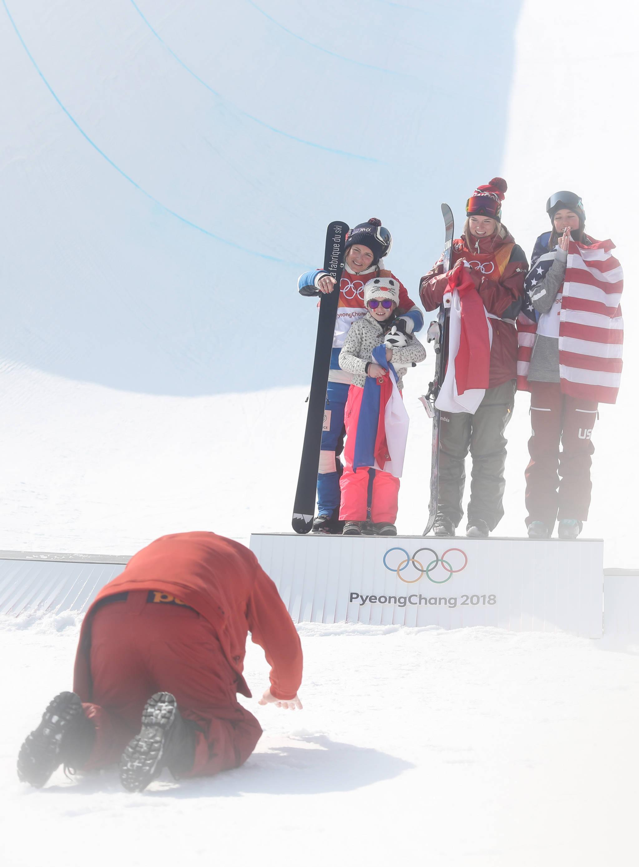 '우리 부인 최고'  20일 강원 평창 휘닉스 스노 경기장에서 열린 2018 평창동계올림픽 여자 스키 하프파이프 결승에서 금메달을 딴 캐나다의 캐시 샤페(가운데), 은메달을 딴 프랑스의 마리 마르티노(왼쪽), 동메달을 딴 미국의 브리타 시고니가 시상대에서 활짝 웃는 동안 마리 마리노의 남편이 절을 하고 있다. 마리 마르티노 오른쪽은 딸이다.