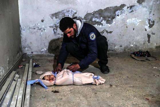 22일 시리아 반군이 장악한 동(東) 구타 지역 두마에서 한 자원봉사자가 시리아 정부군의 공습으로 숨진 2살 어린이의 시신을 포대에 싸서 묶고 있다. 이 마을에선 정부군 공습으로 25명 이상이 사망한 것으로 전해졌다. [EPA=연합뉴스]