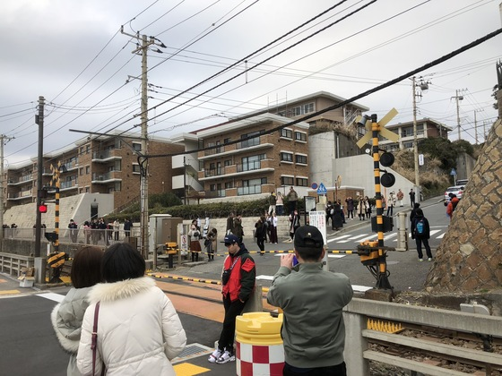 25일 쌀쌀한 날씨에도 불구하고 중국인 관광객들이 일본 가마쿠라시 '가마쿠라 고교역'에서 만화 '슬램덩크'의 배경이 된 학교 주변을 찍고 있다.[사진=서승욱 특파원]
