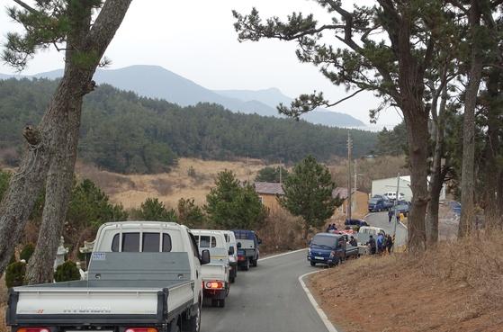 제물을 당에 올려 보내고 남은 고기는 마을 8개 반이 가구수에 맞춰 공평하게 나눈다. 이장이 안내방송을 하자 반 대표자들이 트럭을 몰고 모였다. 사람과 트럭 수가 거의 같았다. 가운데 왼쪽 트럭에서는 고기를 분배하고, 오른쪽에서는 고기를 잘라 굽고 있다. 건너편에 보이는 산은 보길도다.