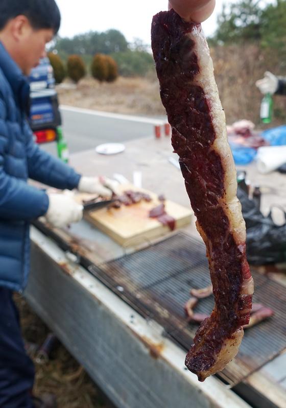 즉석에서 나무들을 주워 모아 일군 화톳불에 잘 구워진 고기.