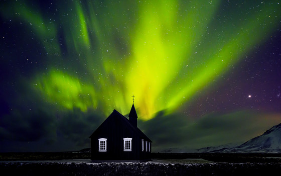Beautiful bright green Northern light over church, little village in the Iceland, amazing forces of nature, wonderful night sky landscape