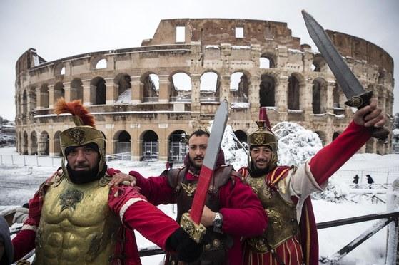 26일(현지시간) 폭설로 눈이 내린 이탈리아 로마의 콜로세움 앞에서 고대 로마 병사 복장을 한 남자들이 포즈를 취하고 있다.[사진 EPA]