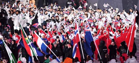 남·북 선수단이 25일 오후 강원도 평창 올림픽스타디움에서 열린 폐회식에서 입장하고 있다. 이날 흰 패딩을 입은 대한민국 선수들은 태극기를, 붉은색 유니폼을 입은 북한 선수는 인공기와 한반도기를 흔들며 입장했다. [오종택 기자]