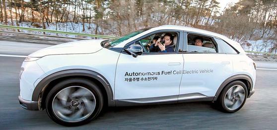 현대자동차 자율주행 수소전기차가 고속도로를 질주하는 가운데 운전자가 카메라로 창문 밖 풍경을 찍고 있다. 현대·기아차는 현재 13종인 전동화차량을 2025년까지 38종으로 확대해 세계 친환경차 시장 2위를 달성할 방침이다. [사진 현대자동차그룹]