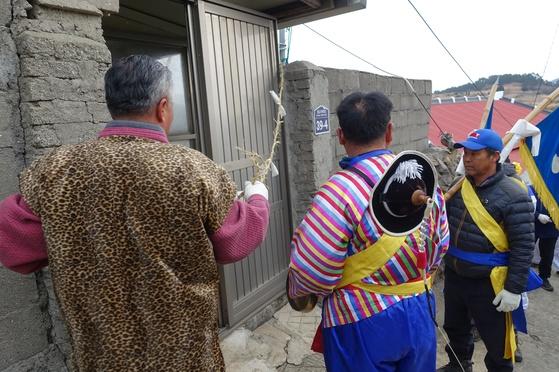 농악대는 집돌이를 유사의 집부터 시작한다. 농악대 길잡이인 포수가 용 유사 집에 친 금줄을 걷고 있다.