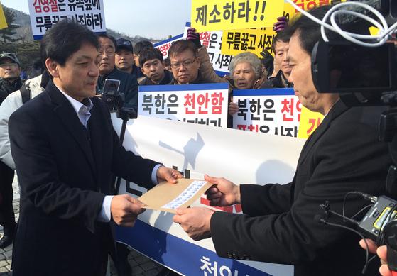 박진원 청와대 통일정책비서실 선임행정관이 유족들로부터 항의서한을 받고 있다. 오원석 기자