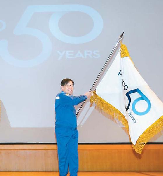 포스코 권오준 회장은 지난달 2일 열린 시무식에서 창립 50주년 공식 엠블럼을 선포했다. 권 회장이 엠블럼 깃발을 흔들고 있는 모습. [사진 포스코]