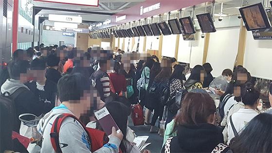 인천공항 면세품 인도장 앞에 긴 줄이 늘어서 있다. [사진 독자제공]
