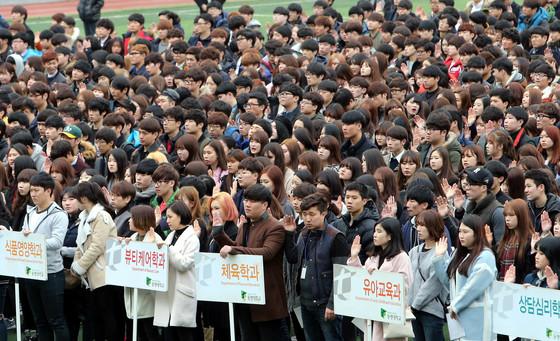 지난 23일 부산 남구 동명대 운동장에서 열린 입학식에서 신입생 2160명이 입학선서를 하고 있다. [중앙포토]