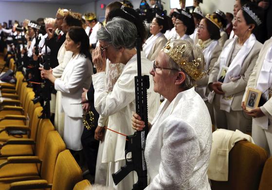 지난달 28일 미국 펜실베이니아주 뉴파운드랜드에 있는 '세계평화통일안식처' 교회에서 열린 합동결혼식 참석자들의 모습. 머리에 왕관을 쓴 참석자들의 손에 AR-15 소총이 들려 있다. [뉴파운드랜드 AP=연합뉴스]