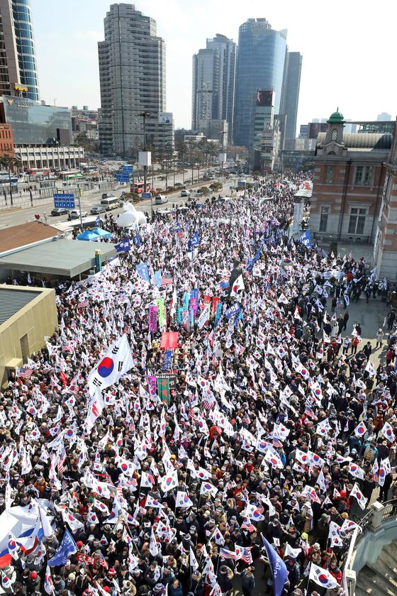 대한애국당 등 보수단체 회원 7000여 명이 1일 오후 서울역 광장에서 '태극기집회'를 열고 박근혜 전 대통령의 석방을 촉구하고 있다. 이들은 태극기와 성조기를 흔들며 세종문화회관까지 행진을 벌였다. [뉴스1]