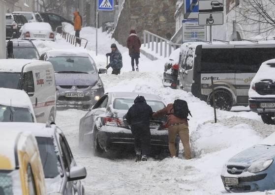 유럽 전역에 시베리아 한파가 몰아친 1일(현지시간) 우크라이나 키예프에서 시민들이 눈길 위에 고립된 차를 밀고 있다. 이번 혹한과 폭설로 폴란드에서만 21명이 사망했고 영국·네덜란드·프랑스·스페인 등 유럽 전역에서 최소 55명이 사망한 것으로 AFP는 보도했다. [EPA=연합뉴스]