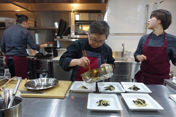 불고기와 능이죽순채를 준비하는 주방. 능이죽순채 담기가 끝나가자 여자 보조요리사가 불고기가 구워진 진도를 살피고 있다.