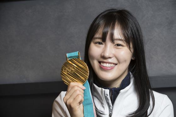 김아랑이 여자 쇼트트랙 3000m 계주에서 딴 금메달을 내보이며 활짝 웃고 있다. 그는 쇼트트랙 1500m에서 4위로 골인한 뒤에도 밝은 미소를 지어 박수를 받았다. [우상조 기자]