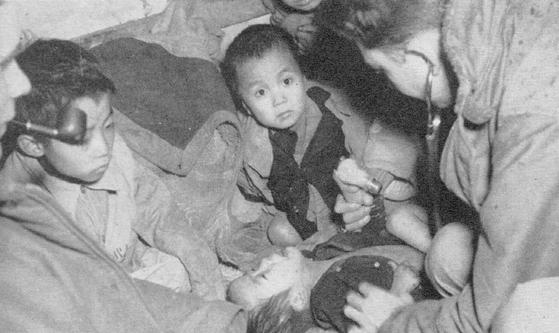 고아들의 건강 상태를 살피는 군의관. 당시 원생들은 세인트 폴의 승조원들을 어느 날 갑자기 나타난 천사라고 생각했다. [http://cid169.kwva.org]