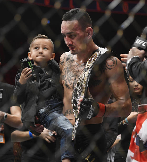 Max Holloway holds his son Rush, after Holloway defeated Jose Aldo, of Brazil, during a UFC 218 featherweight mixed martial arts bout, early Sunday, Dec. 3, 2017, in Detroit. (AP Photo/Jose Juarez) <저작권자(c) 연합뉴스, 무단 전재-재배포 금지>