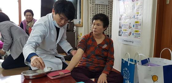 천안시 병천면 탑원리 마을회관에서 할머니에게 침을 놓고 있는 한의사 이경구씨. [신진호 기자]