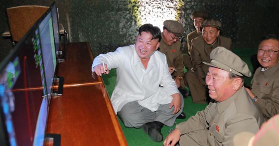 김정은 북한 노동당 위원장이 SLBM 시험 발사 장면을 지켜보면서 담배를 든채 미사일 성공을 주도한 이병철 당 제1부부장과 함께 기뻐하고 있다. [사진 노동신문]