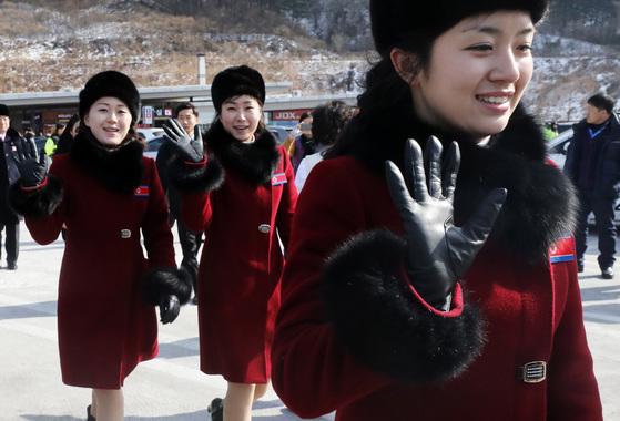 평창동계올림픽에 참가하기 위해 방남한 북한 응원단 여성들이 7일 오전 경기도 가평군 가평휴게소에 잠시 정차해 이동하며 취재진에게 손인사를 하고 있다. [뉴스1]