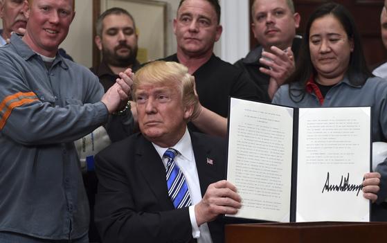 도널드 트럼프 미국 대통령이 8일(현지시간) 미국내 철강ㆍ알루미늄업체 노동자들이 지켜보는 가운데 수입제품에 관세를 부과하는 행정명령에 서명한 뒤 들어보이고 있다. [AP=연합뉴스]