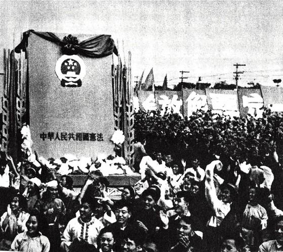중국 최초의 헌법이 공포된 1954년 건국기념일 행사에서 군중들이 대형 헌법모형을 앞세우고 천안문 광장 앞 대로를 행진했다. [중국 외문출판사]