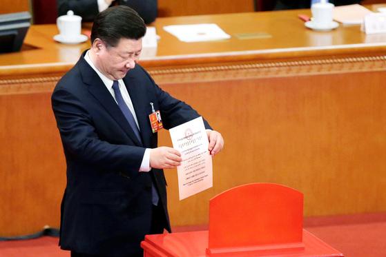 11일 베이징 인민대회당에서 열린 전국인민대표대회 제3차 전체회의에 참석한 시진핑 중국 국가주석이 '중화인민공화국 헌법 개정안 초안 표결용지'라고 쓰인 투표용지를 함에 넣고 있다. [로이터=연합뉴스]
