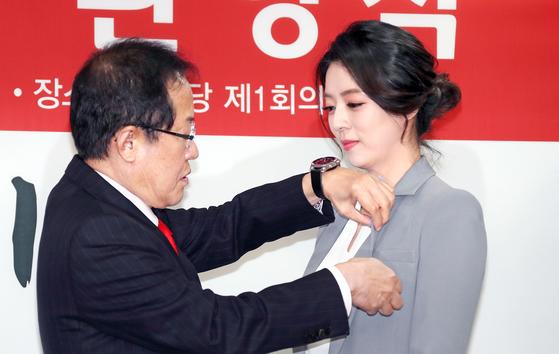 홍준표 대표(왼쪽)가 9일 당사에서 배현진 전 MBC 앵커에게 태극기 배지를 달아주고 있다. [중앙포토]