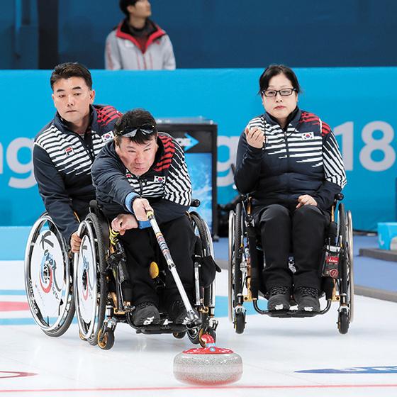 한국 휠체어 컬링 대표팀 정승원(가운데)이 12일 캐나다전에서 스톤을 밀고 있다. 그 뒤에서 차재관이 휠체어가 밀리지 않도록 바퀴를 잡고 있다. 방민자(오른쪽)는 초시계를 보며 샷 속도를 확인하고 있다. 한국은 풀리그로 진행되는 예선에서 4연승으로 12개 팀 중 1위다. [뉴시스]