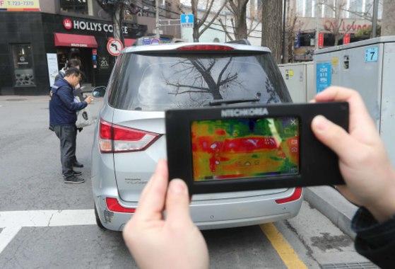 서울시 공회전 단속반이 지난 9일 서울 종로구에서 한 승용차를 단속하고 있다. 열화상 카메라 기기 화면에 엔진을 켠 승용차가 붉게 나타났다. [김상선 기자]