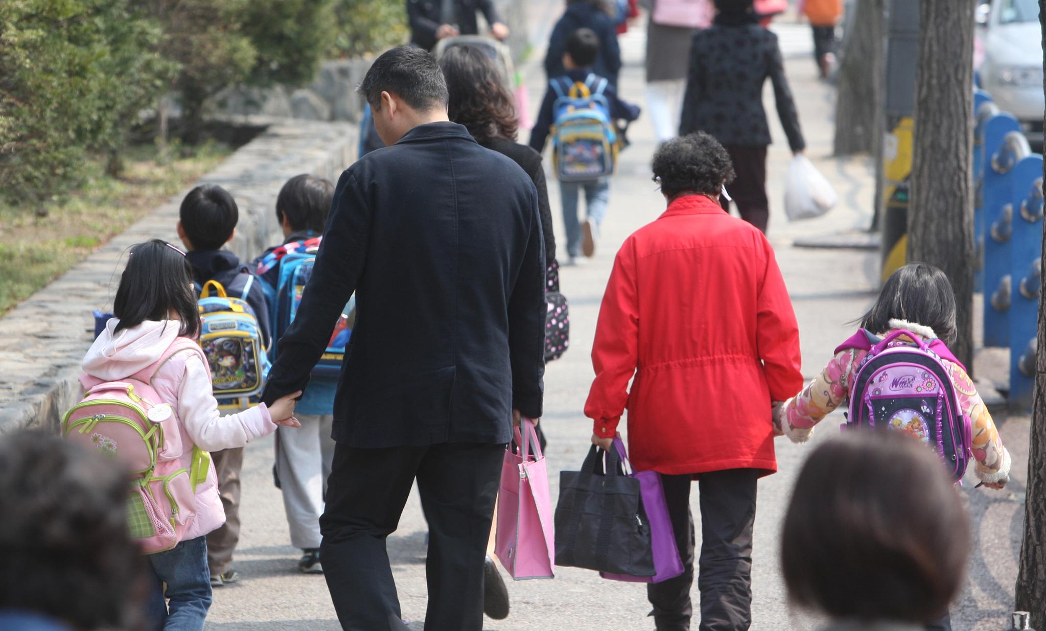 초등학생 자녀의 손을 잡고 함께 하교하는 학부모들. [중앙포토]