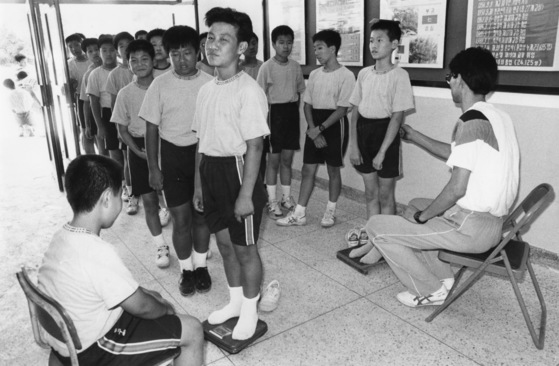 학교 신체검사에서 키와 몸무게를 재고 있는 남자 중학생들. [중앙포토]