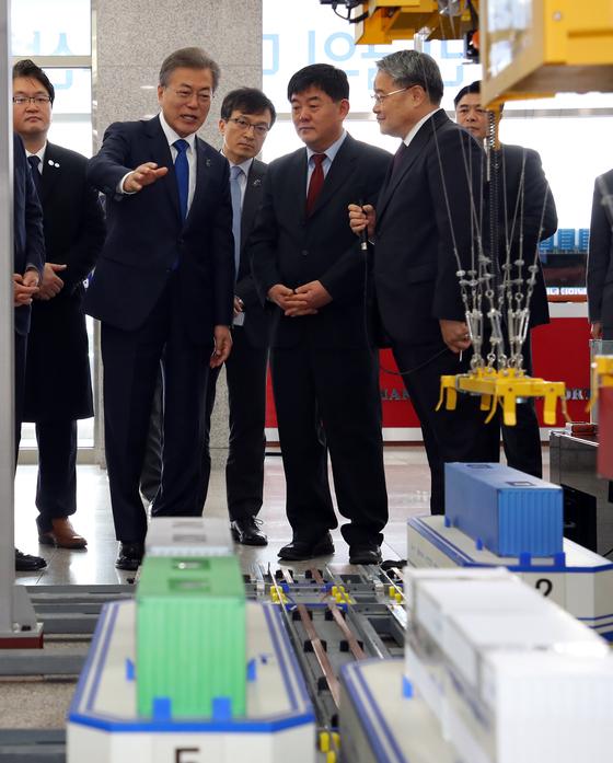 문재인 대통령이 16일 오전 부산 신항을 방문해 자동화 컨테이너터미널 모형 앞에서 현황을 보고 받고 있다. [연합뉴스]