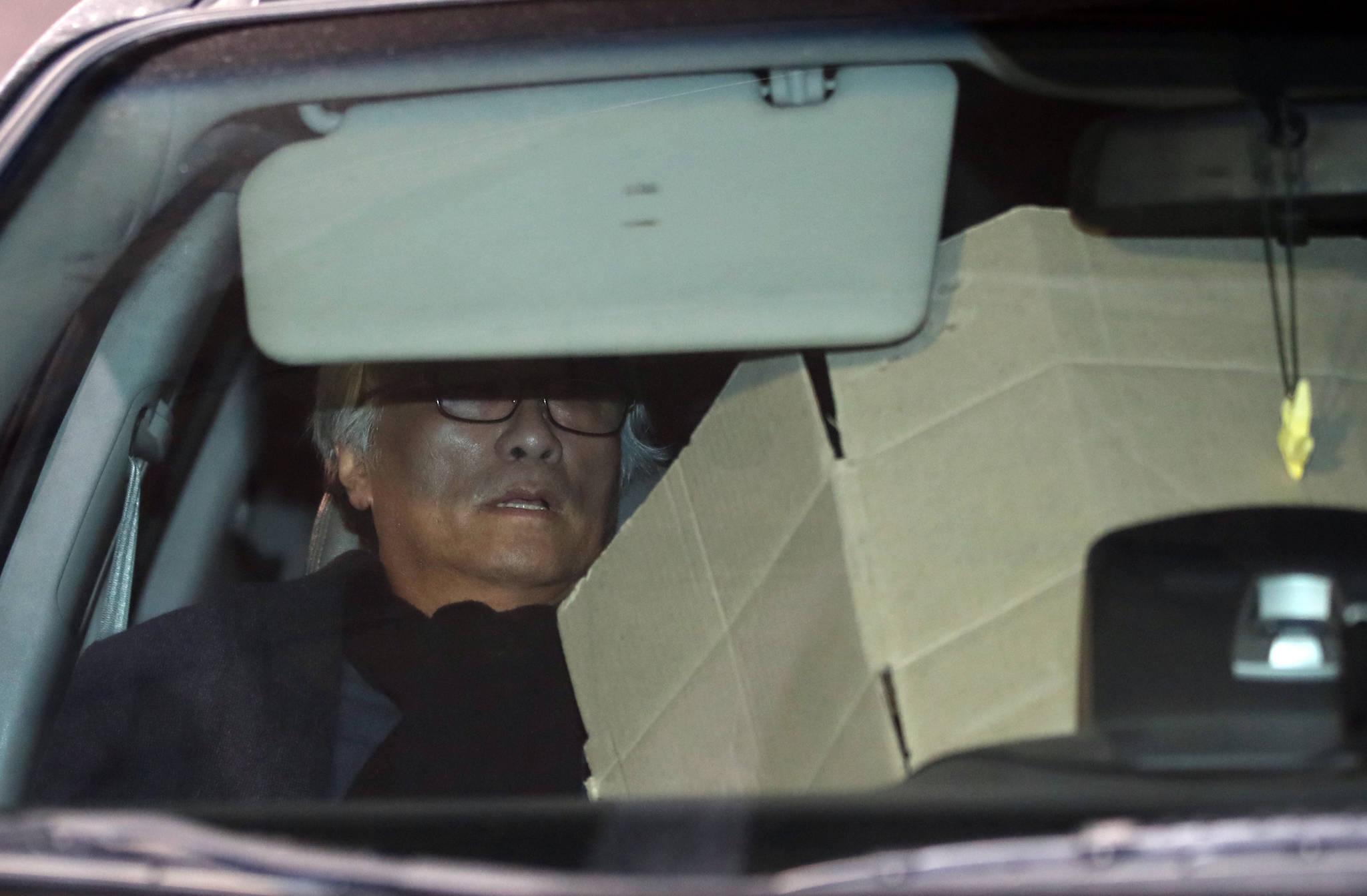 극단 단원에게 상습적으로 성폭력을 가한 의혹을 받는 연극연출가 이윤택씨가 18일 오전 서울 종로구 서울지방경찰청에서 조사를 받은 뒤 귀가하는 차에 올라 종이박스로 얼굴을 가리고 있다. [연합뉴스]