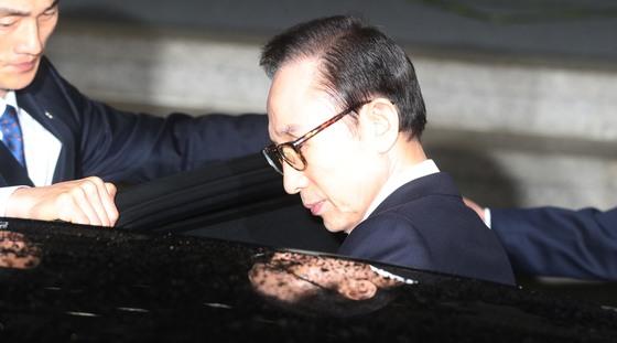 이명박 전 대통령이 15일 서울중앙지검에서 밤샘조사를 받은 뒤 귀가를 위해 차량에 타고 있다. [중앙포토]