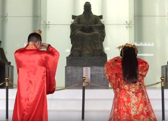 전통적인 유교 방식으로 결혼식을 하는 부부가 공자의 동상에 절을 하고 있다.[WSJ 유튜브 캡처]