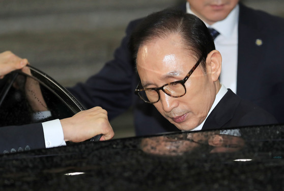 서울 서초동 서울중앙지검에 출석해 만 하루에 가까운 21시간 만에 조사를 마친 이명박(77) 전 대통령이 지난 15일 오전 6시 25분에 검찰청사를 나서며 차에 오르고 있다. 이혜경 기자