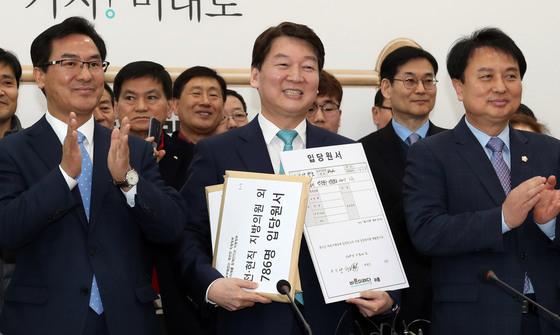 자유한국당 소속 전·현직 수도권 지역 지방의회 의원 7명이 한국당을 탈당해 바른미래당에 22일 입당했다. 이들과 함께 한국당과 더불어민주당 당원 786명이 바른미래당에 합류했다. 안철수 바른미래당 인재영입위원장(가운데)이 22일 서울 여의도 국회에서 열린 인재영입 발표식에서 양창호 전 의원으로부터 입당원서를 받고 있다. 변선구 기자