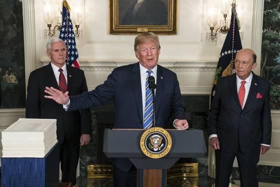 도널드 트럼프 미국 대통령은 23일(현지시간) 백악관에서 열린 2018회계연도 지출예산 서명식에서 한국과의 통상협상 종료가 매우 가까워졌다고 밝혔다. 왼쪽부터 마이크 펜스 부통령, 트럼프 대통령, 윌버 로스 상무장관.[워싱턴 EPA=연합뉴스]