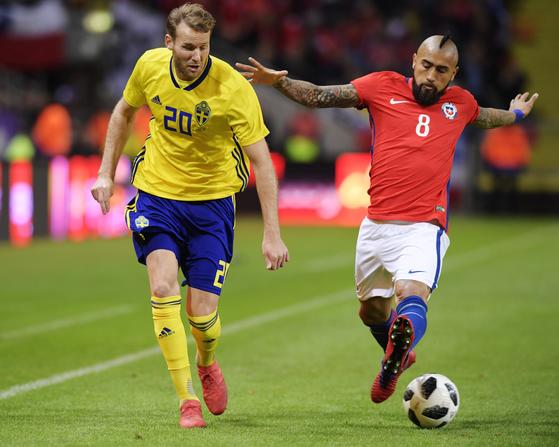 스웨덴의 올라 토이보넨(왼쪽)이 25일 스웨덴 스톡홀름에서 열린 A매치 평가전에서 칠레의 아르투로 비달과 공을 다투고 있다. [스톡홀름 AP=연합뉴스]