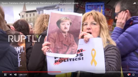 푸지데몬 전 수반의 구금에 항의하기 위해 나선 시민. 앙겔라 메르켈 독일 총리의 사진에 히틀러를 상징하는 콧수염이 합성돼 있다. [사진=유튜브 캡처]