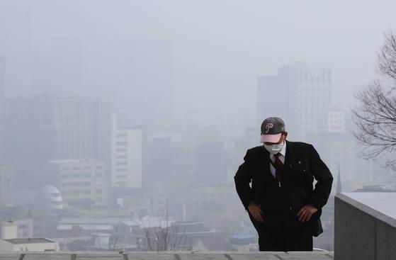 미세먼지 농도가 '나쁨' 수준을 보인 26일 오전 마스크를 낀 한 시민이 서울 중구 남산도서관으로 향하는 계단을 오르고 있다. [연합뉴스]