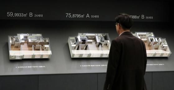 기존 집값이 크게 오른 반면 신규 분양 아파트 가격은 주변 시세보다 저렴해 청약경쟁이 치열하다. 수도권 모델하우스에서 방문객이 아파트 단지 모형을 살펴보고 있다.