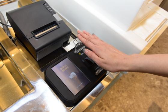 롯데시네마가 13일 국내 영화관 최초로 정맥정보 인식 지불 방식을 도입했다. 카드센터에서 소지한 롯데카드에 정맥정보를 등록한 후 결제 시 손바닥만 기기에 대면 카드에서 돈이 자동으로 빠져나가는 방식이다. [사진 롯데시네마]