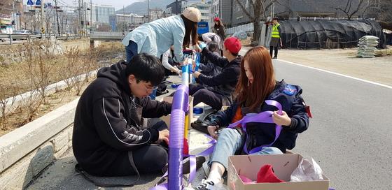 27일 오전 백석대 영상디자인학부 학생들이 천안시 안서동 문암3교 도로변에 설치된 안전봉에 패브릭 천을 감고 있다. 신진호 기자