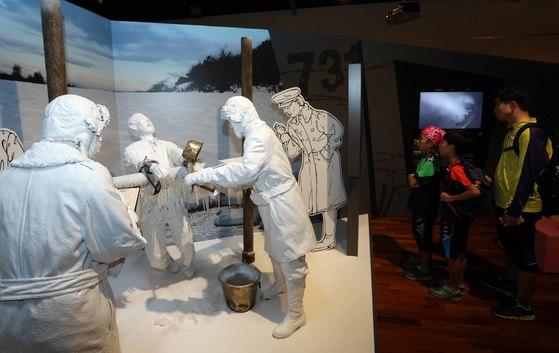 지난 2013년 일본 관동군 제731부대가 현지에서 벌인 잔혹한 실상을 보여주는 특별전이 천안 독립기념관 특별전시설에서 열렸다. 전시장을 찾은 한 가족이 731부대원들이 살아 있는 사람을 냉동시키는 장면을 연출한 입체물을 지켜보고 있다.[중앙포토]
