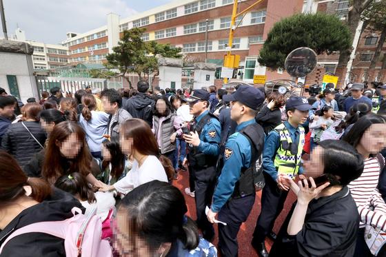 """인질극 소식을 접한 방배초등학교 학부모들이 2일 학교 정문 앞에서 자녀를 기다리고 있다. 경찰에 체포된 범인은 '군대에서 질병이 생겼는데 아무도 보상을 해주지 않아서 범행했다""""고 말했다. [뉴스1]"""