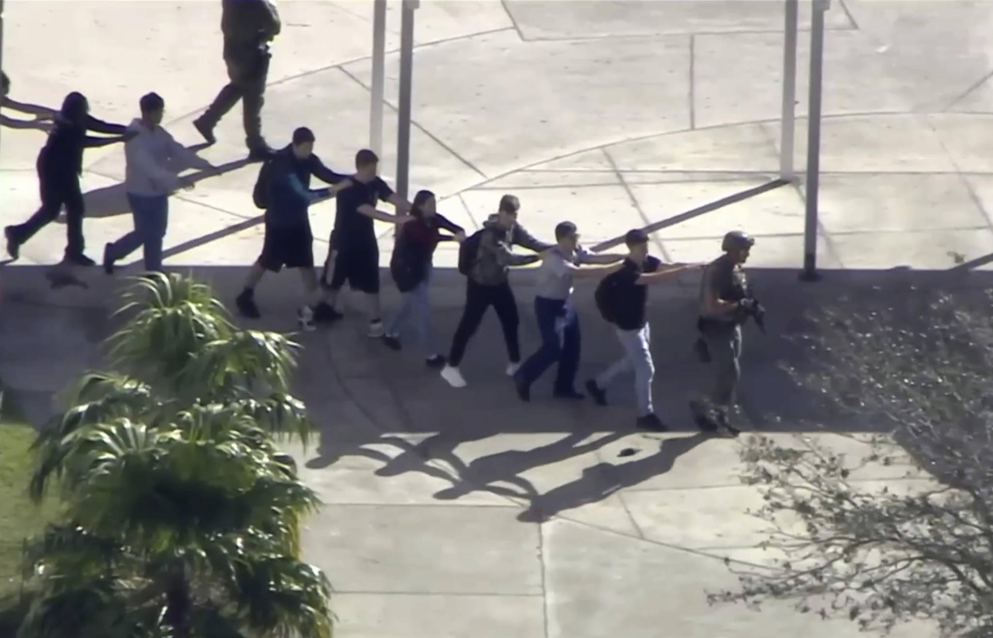 총격 난사 사건이 일어난 마조리 더글라스 고등학교 학생들이 지난 14일(현지시간) 경찰의 보호를 받으며 학교에서 탈출하고 있다. [로이터=연합뉴스]