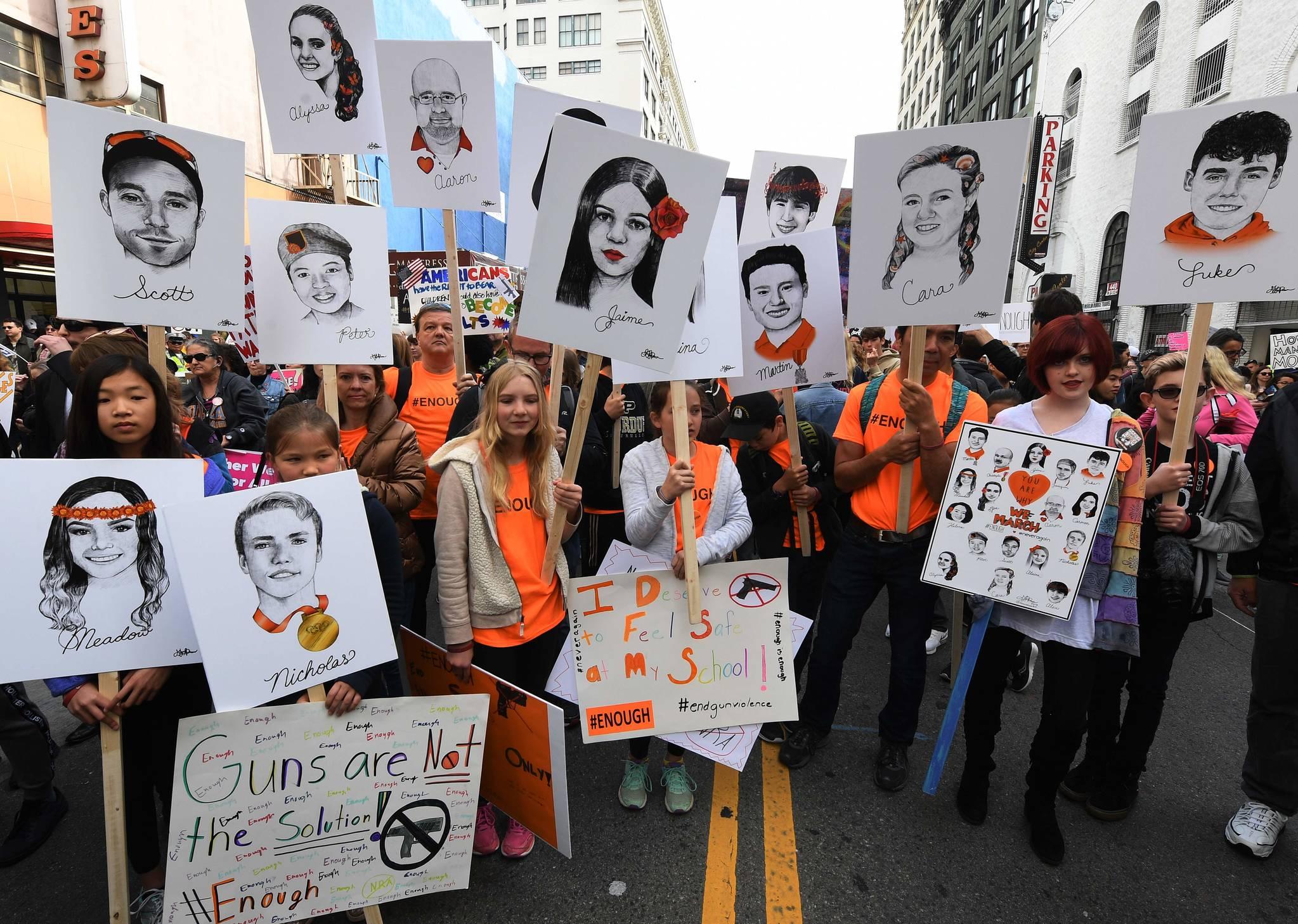지난 3월 24일(현지시간) 워싱턴에서 총기 규제를 요구하며 '우리의 생명을 위한 행진'에 참가한 시민들이 희생자들의 얼굴이 그려진 손팻말을 들고 있다. [AFP=연합뉴스]